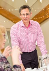 Mike from Griffin House Consultancy stood listening to a delegate at a training session.