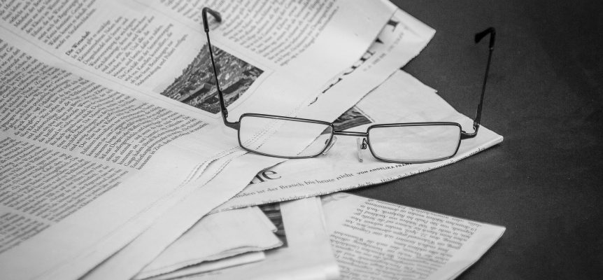 Open pair of glasses sat on a pile of newspapers.