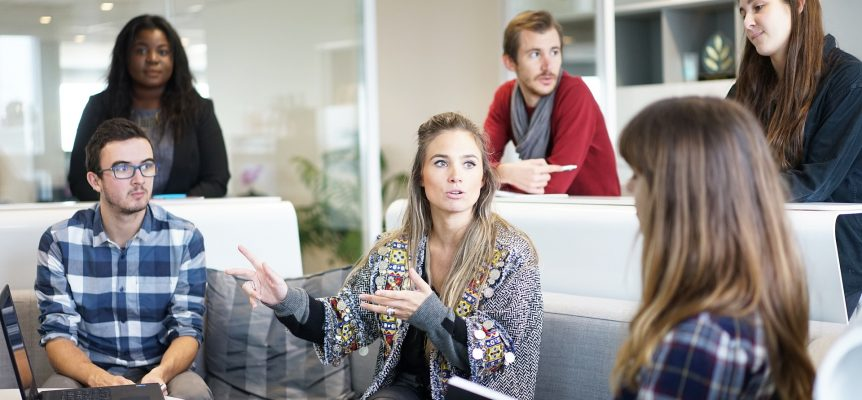Team of employees sat around in a meeting and listening to someone talk.